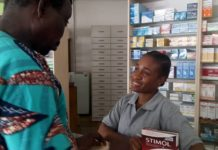 Une vendeuse en pharmacie servant un client