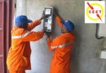Des techniciens de la CEET montent un compteur d'électricité